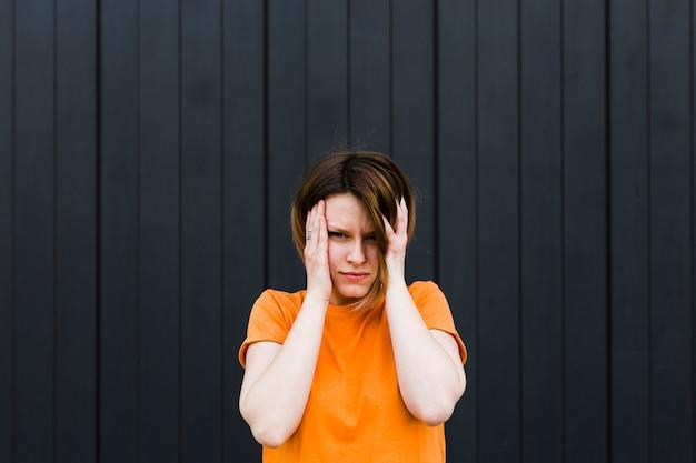 Mujer joven frustrada contra el fondo rayado negro