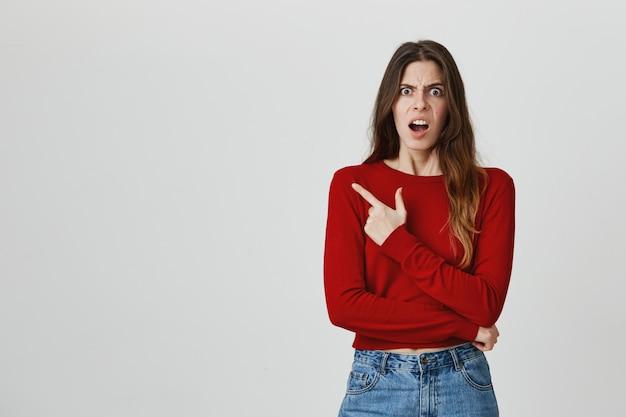 Mujer joven frustrada y enojada que señala el dedo esquina superior izquierda con la cara sorprendida