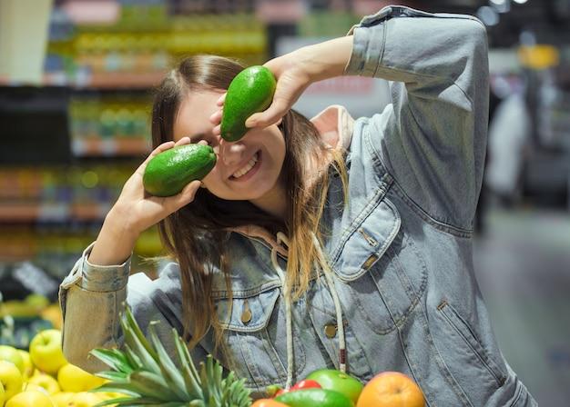 Mujer joven con fruta en sus manos en el supermercado.