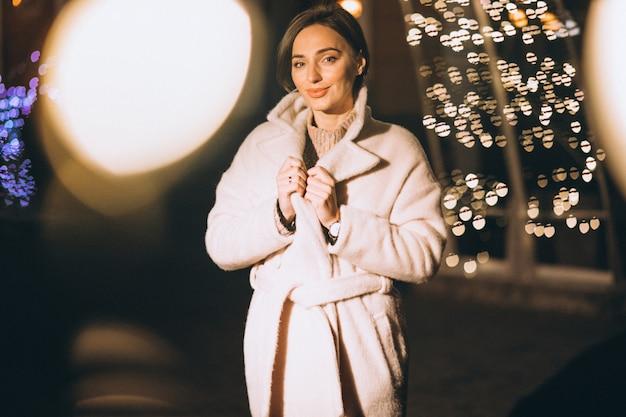 Mujer joven fuera de la calle de noche con luces