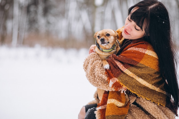 Mujer joven fuera del parque con su perrito en invierno