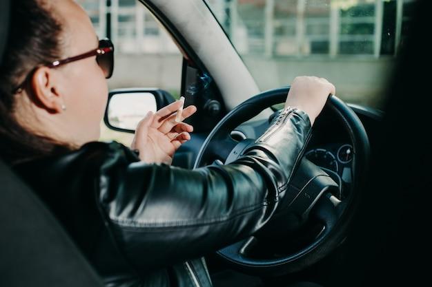 Mujer joven fumando un cigarrillo mientras conduce un automóvil, concepto de transporte