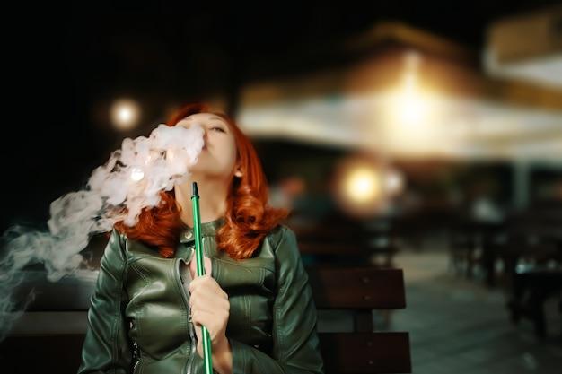 Mujer joven fumando narguile en el bar salón