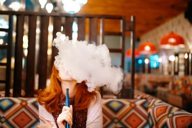 Mujer joven fumando narguile en el restaurante