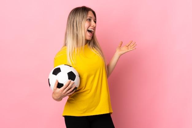 Mujer joven futbolista aislada en rosa con expresión facial sorpresa