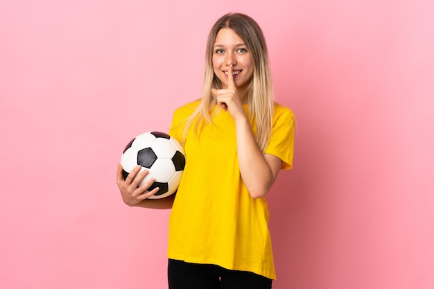 Mujer joven futbolista aislada en rosa haciendo gesto de silencio