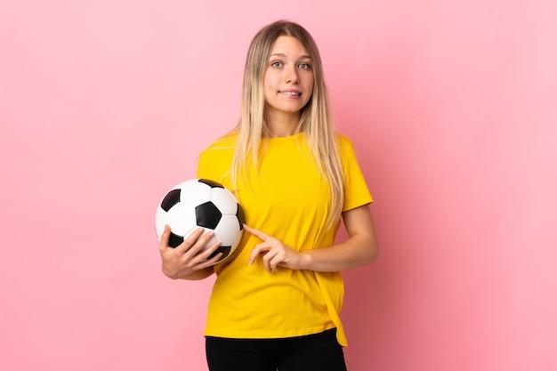 Mujer joven futbolista aislada en rosa que tiene dudas con expresión de la cara confusa