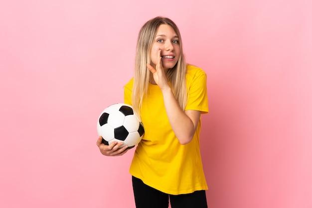 Mujer joven futbolista aislada en rosa susurrando algo