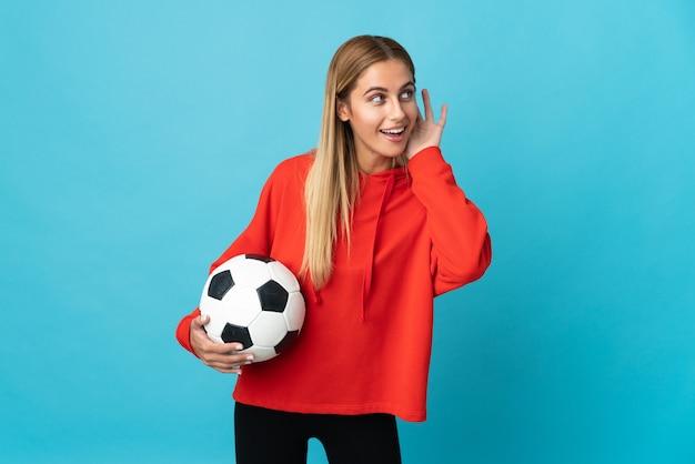 Mujer joven futbolista en azul escuchando algo poniendo la mano en la oreja