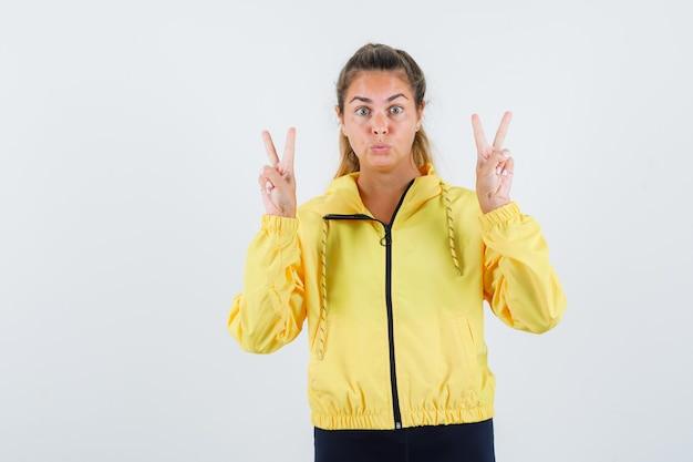 Mujer joven en gabardina amarilla mostrando gesto de victoria