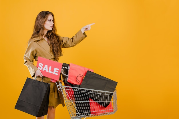 Mujer joven en gabardina apuntando a copyspace con cartel de venta y coloridas bolsas de compras en carro aislado sobre amarillo