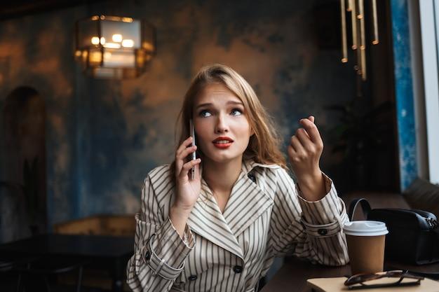 Mujer joven en gabardina a rayas hablando por teléfono celular pensativamente