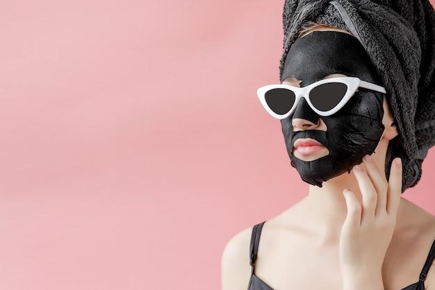Mujer joven en gafas appling máscara facial de tela cosmética negra sobre fondo rosa. mascarilla exfoliante con carbón, tratamiento de belleza spa, cuidado de la piel, cosmetología. de cerca
