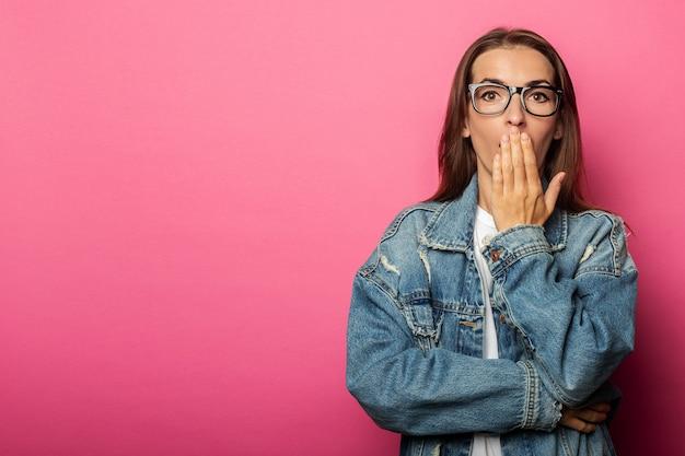 Mujer joven con gafas bosteza tapándose la boca con la palma