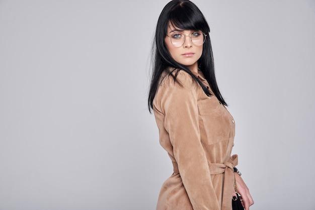 Mujer joven con gafas, elegante vestido marrón. chica posando en una pared gris. peinado. chica con bolso negro. foto de moda