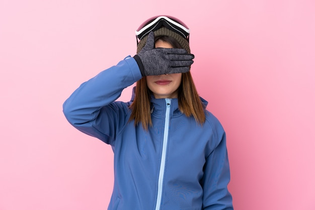 Mujer joven con gafas de esquí sobre pared rosa