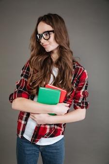 Mujer joven con gafas con libros en las manos.