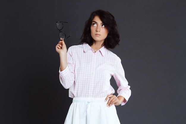 Mujer joven con gafas en la mano posando sobre pared gris