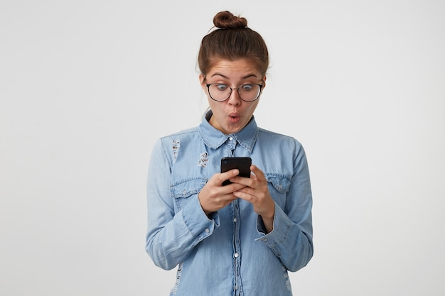 Mujer joven con gafas está mirando, sosteniendo en las manos un teléfono inteligente, con los ojos bien abiertos y la boca redondeada en sorpresa