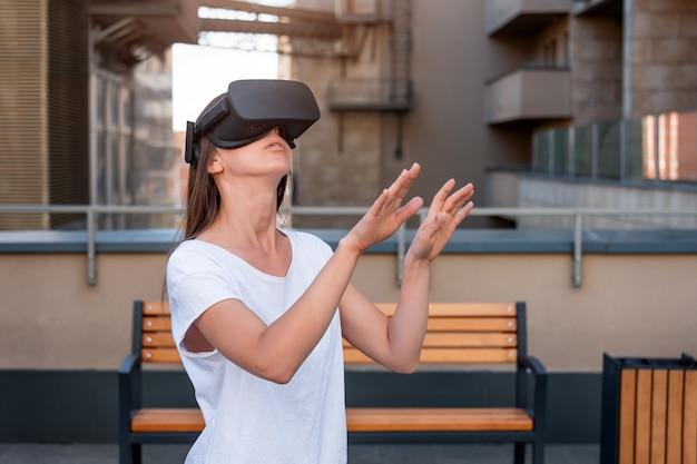 Mujer joven con gafas de realidad virtual auriculares, caja vr al aire libre. conexión, tecnología, nueva generación, concepto de progreso. chica tratando de tocar objetos en realidad virtual