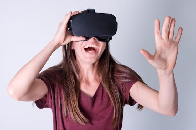 Mujer joven con gafas de realidad virtual auriculares, vr box. conexión, tecnología, nueva generación, concepto de progreso. chica tratando de tocar objetos en realidad virtual. foto de estudio en gris