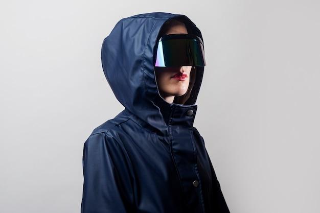 Mujer joven con gafas de realidad virtual en una chaqueta azul con capucha sobre un fondo claro.