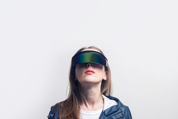 Mujer joven con gafas de realidad virtual en una chaqueta azul mira hacia arriba sobre un fondo claro.