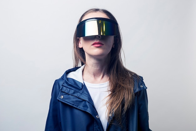 Mujer joven con gafas de realidad virtual en una chaqueta azul sobre un fondo claro.