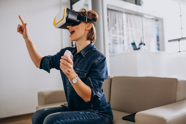 Mujer joven con gafas de realidad virtual y jugando juegos virtuales con control remoto