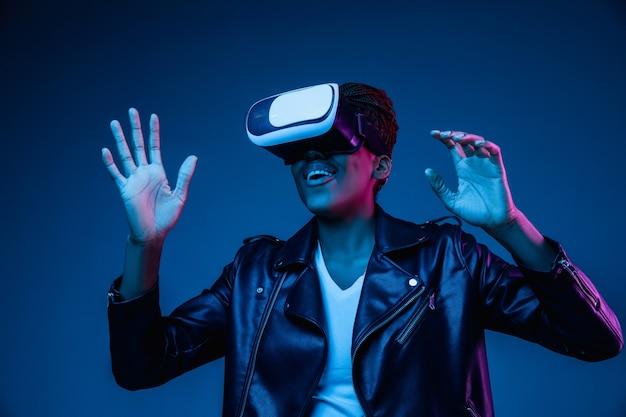 Mujer joven con gafas de realidad virtual con luces de neón