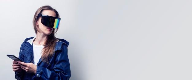 Mujer joven en gafas de realidad virtual con un teléfono en una chaqueta azul sobre un fondo claro. bandera.