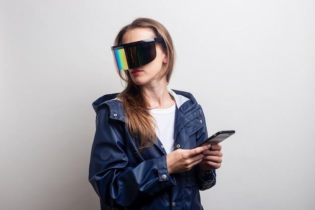Mujer joven en gafas de realidad virtual con un teléfono en una chaqueta azul sobre un fondo claro.