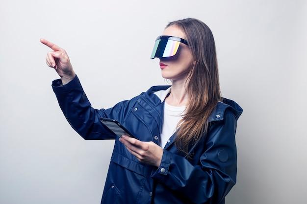 Mujer joven en gafas de realidad virtual con un teléfono señala con el dedo hacia un lado sobre un fondo claro.