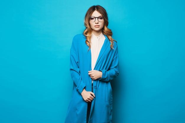 Mujer joven en gafas redondas y abrigo azul, aislado en fondo azul. chica modelo con abrigo azul y gafas de moda sobre fondo azul. copia espacio moda femenina.