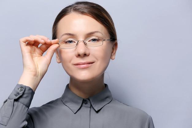 Mujer joven con gafas sobre superficie gris