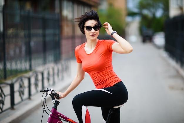 Mujer joven con gafas de sol en bicicleta