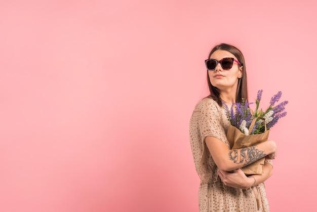 Mujer joven en gafas de sol con bolsa con flores