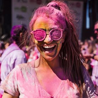 Mujer joven con gafas de sol cubiertas de color holi