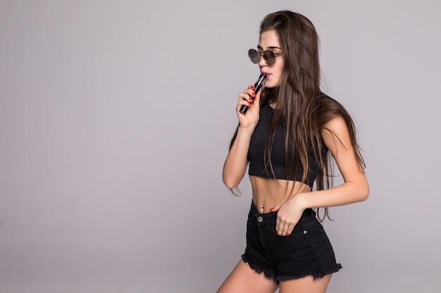 Mujer joven en gafas de sol y ropa negra vaping y soplando humo de cigarrillo electrónico en la pared gris