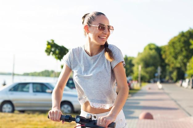 Mujer joven con gafas de sol en scooter