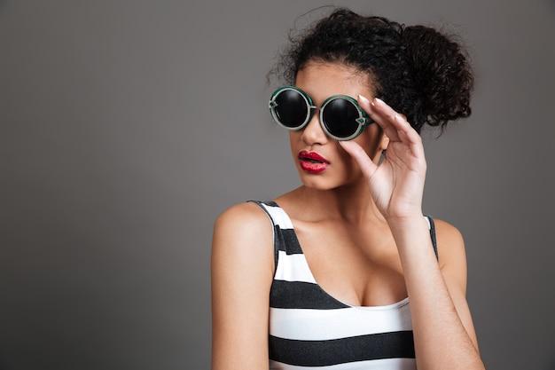 Mujer joven con gafas de sol y vestido a rayas