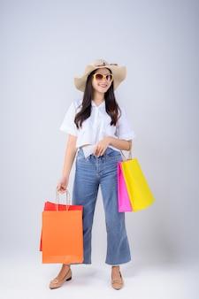 Mujer joven con gafas y un sombrero lleva una bolsa de compras y una factura mientras mira hacia el lado aislado sobre fondo blanco.