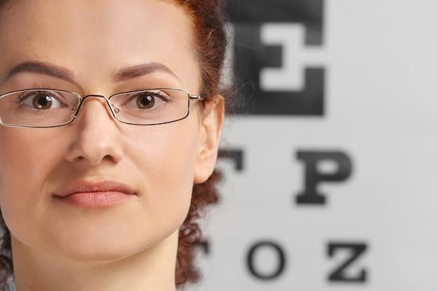 Mujer joven con gafas en la tabla de prueba de la vista