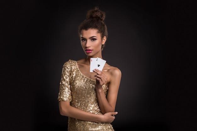Mujer joven ganadora en un elegante vestido dorado sosteniendo dos ases, una combinación de cartas de póquer de ases