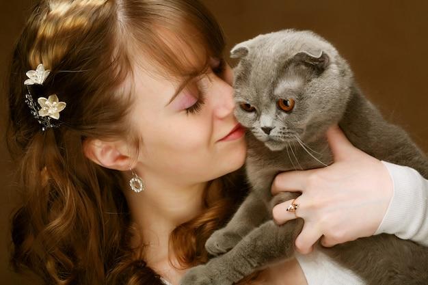 Mujer joven con gato scottish-fold