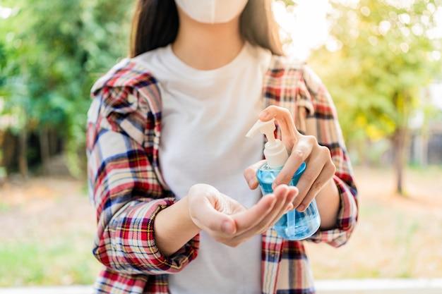 Mujer joven con gel de manos con alcohol antiséptico para limpiar sus manos, árboles borrosos y la pared del jardín