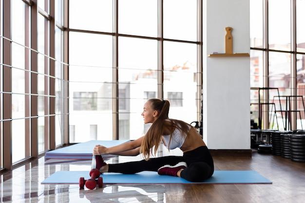 Mujer joven en el gimnasio estirando sobre estera
