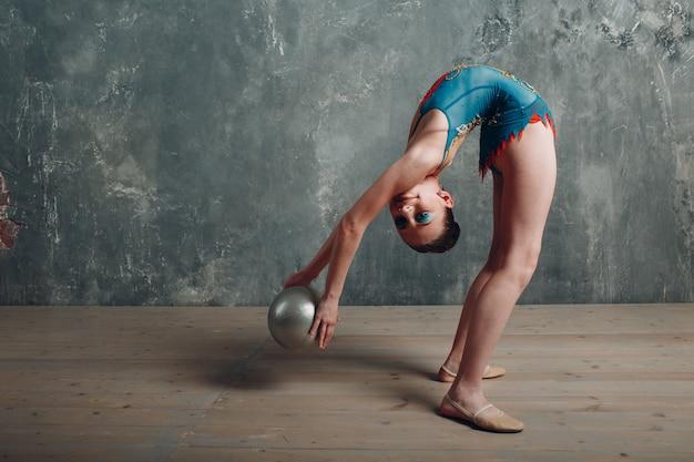 Mujer joven gimnasta profesional danza gimnasia rítmica con bola en el estudio