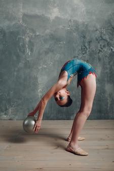 Mujer joven gimnasta profesional danza gimnasia rítmica con pelota en el estudio.