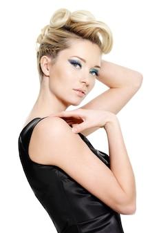 Mujer joven de glamour con maquillaje de ojos azules y peinado rizado sobre fondo blanco
